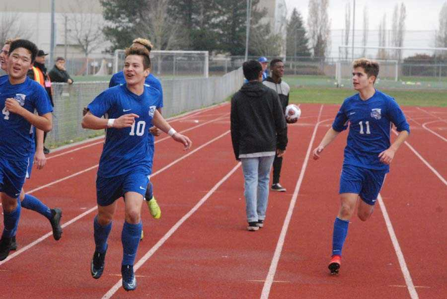 Felipe Rueda (10), flanked by Noah Kim (4) and Elijah Widdows, takes a victory lap after netting the insurance goal for CG