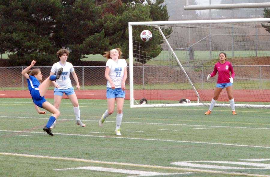 Caroline Cook (in blue) tries an acrobatic shot while Grace Armstrong (14), Wylly Willmott (22) and Izzy Ponce defend