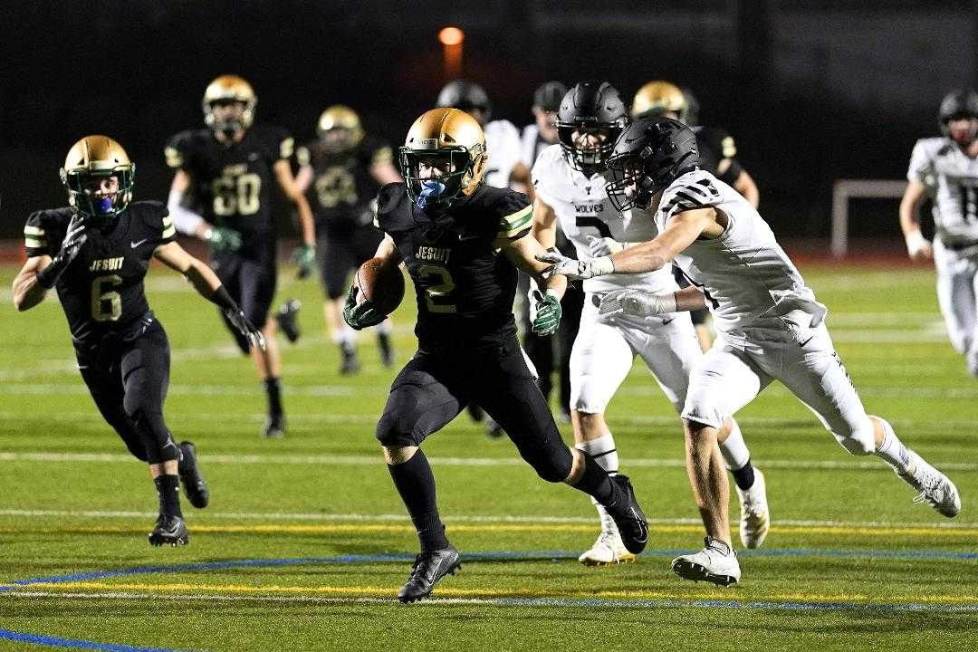 Jesuit's Kade Wisher eludes a defender on the way to one of his four touchdowns Friday night. (Photo by Jon Olson)