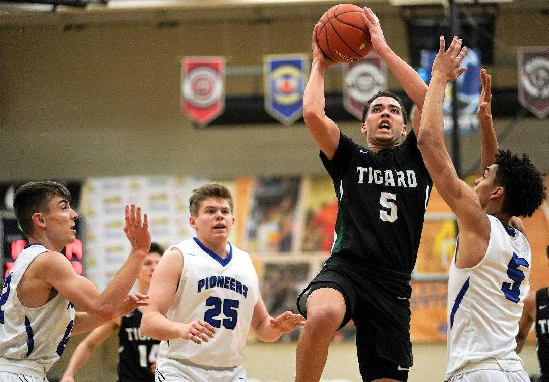 Tigard's Drew Carter rises over Western Christian's Payton Richardson (5) and Darrin Campbell (25). (Photo by Jon Olson)