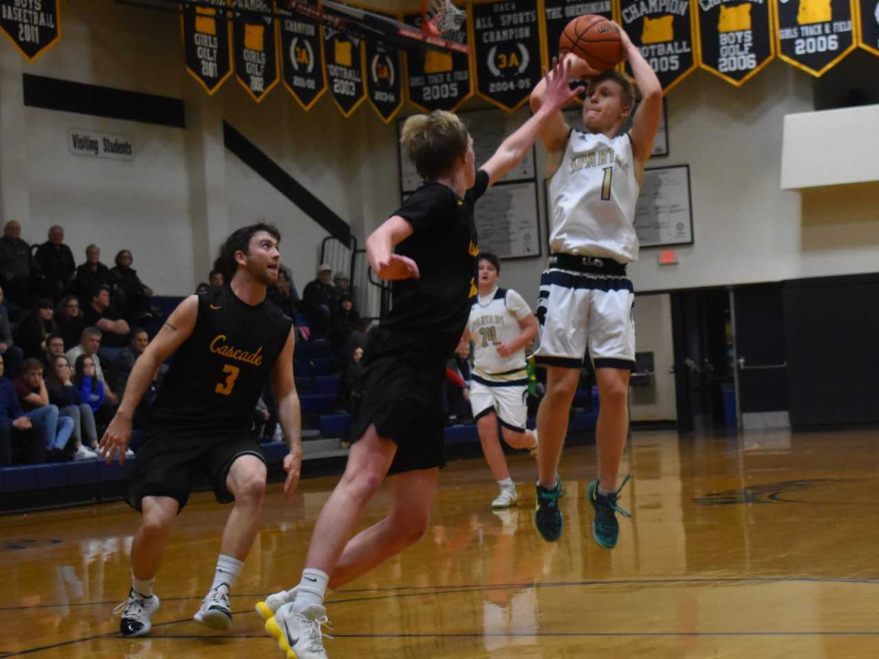 Marist Catholic's Nick Stice shoots over Cascade's Carson Molan on Tuesday night. (Photo by Jeremy McDonald)