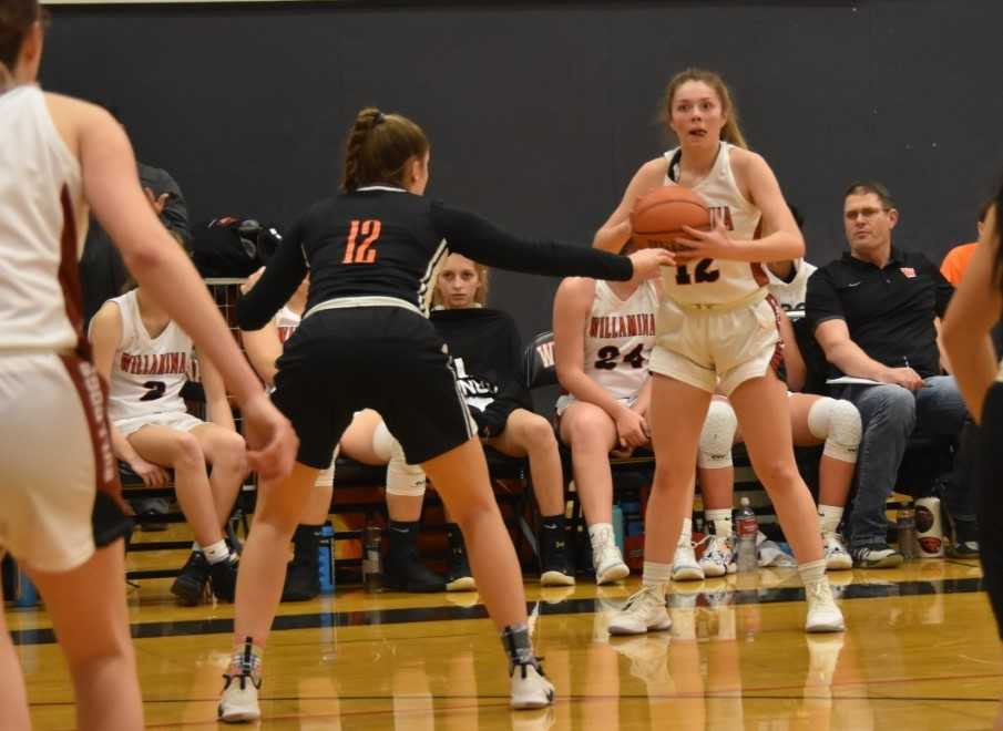 Willamina's Kira Rankin looks to pass against the defense of Taft's Autumn Ellis. (Photo by Jeremy McDonald)