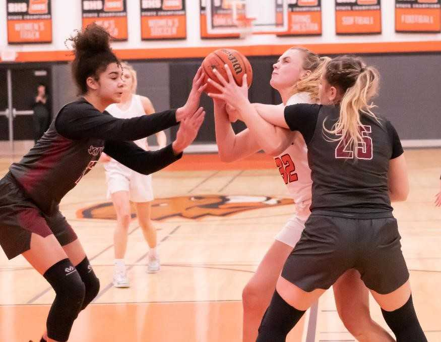 Beaverton's Sydney Erikstrup squeezes between Southridge's Tait Quinlan (left) and Kaylen Blair. (Photo by Gene Schwartz)