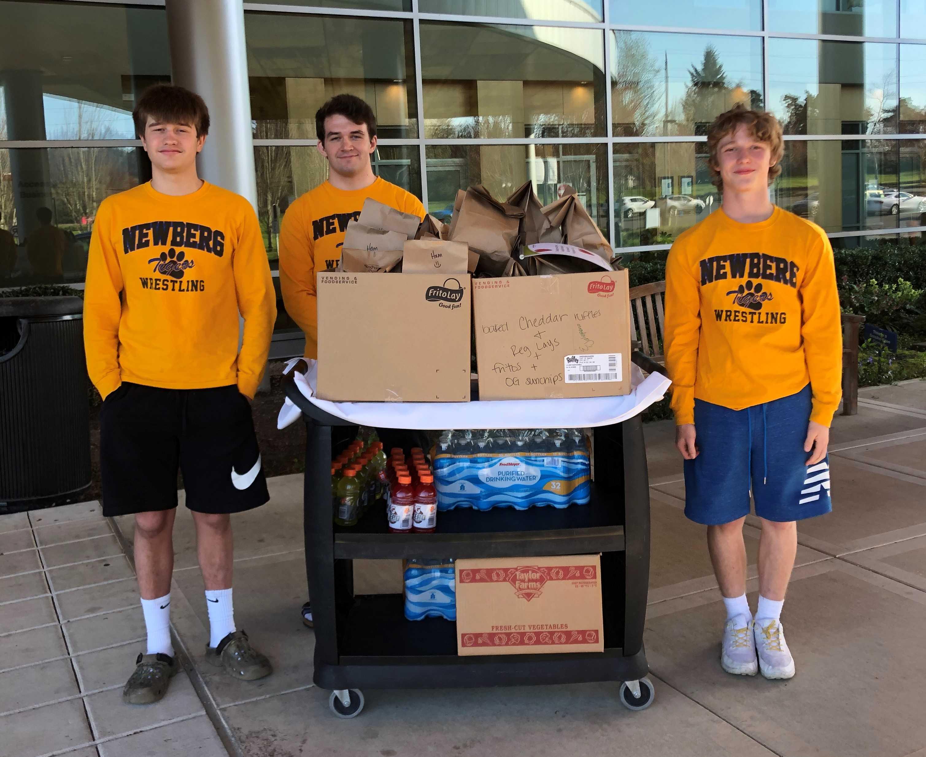 Newberg state champions (from left) Charlie Evans, Hunter James and Ayden Garver deliver meals to the hospital.