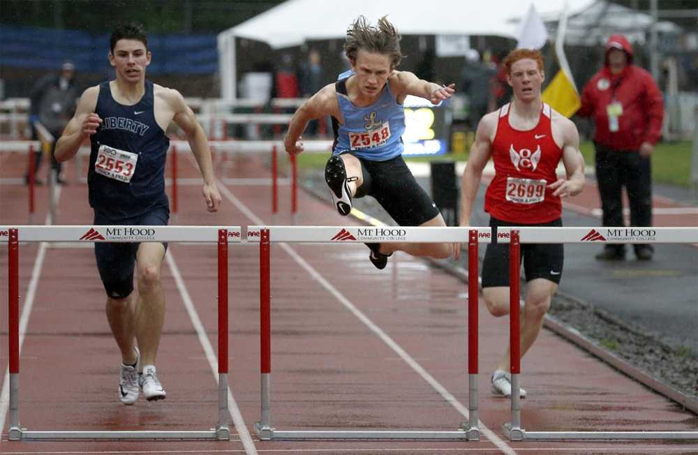 Luke Neville is first over the hurdle in this 100-meter race. Photo by Miles Vance