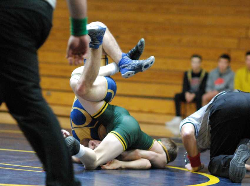 Sophomore Ricky Bell (in green) recorded a technical fall for West Linn at 113 by putting his opponent often on his back
