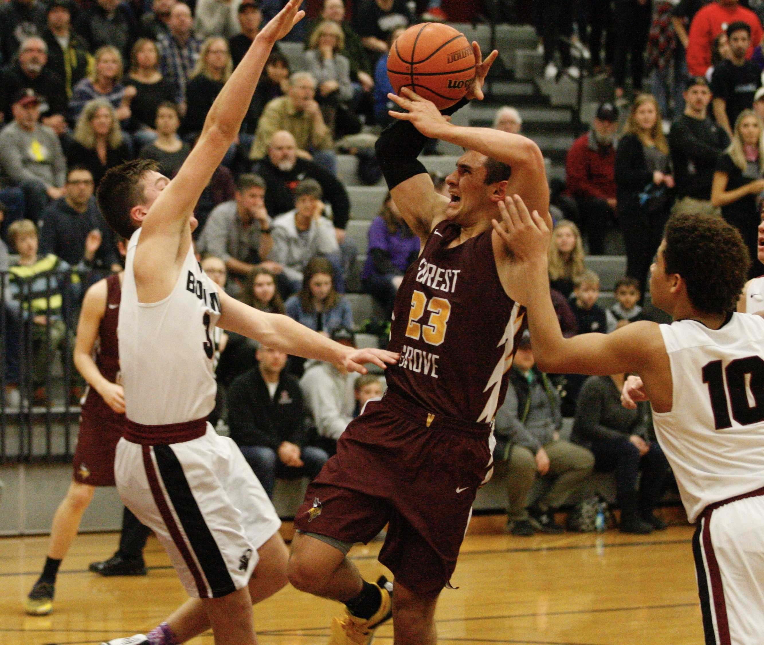 Sherwood defenders Tyler His (3) and Jamison Guerra reject a drive by Forest Grove's Guy Littlefield in decisive third quarter.