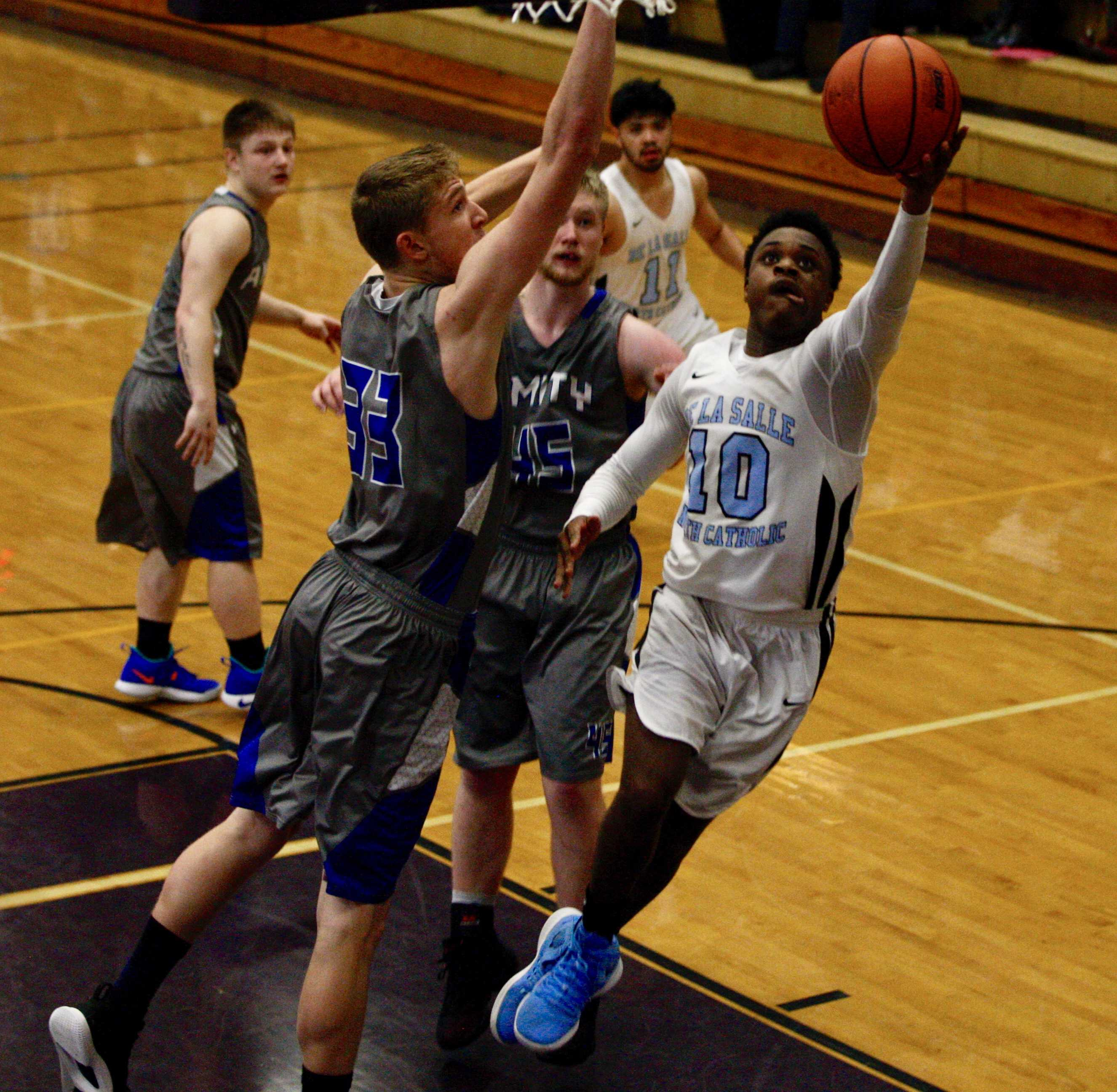De La Salle North Catholic's Anthony Mosley slashes past two Amity defenders to score two of his 18 points (Norm Maves Jr.)