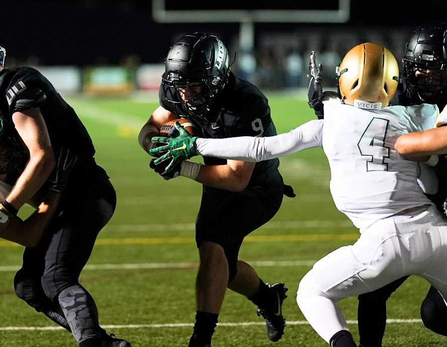 Casey Filkins runs for one of his four touchdowns Friday night against Jesuit. (Photo by Jon Olson)
