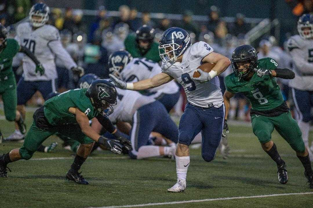 Tigard's Max Lenzy (6) and Josh Burns (8) close in on Lake Oswego's Casey Filkins (9). (Photo by Ralph Greene)