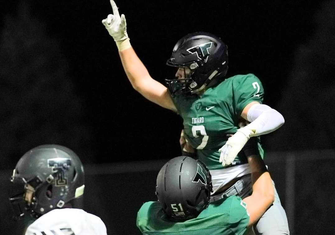 Tigard's Tyler Penn (2) celebrates with Edward Beglaryan after catching a touchdown pass Friday. (Photo by Jon Olson)