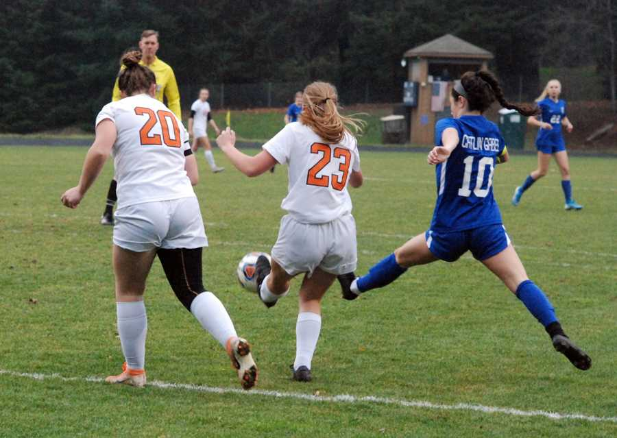 Ann Louise Naito (10) works to poke a pass past Yamhill-Carlton players Julie Easton (23) and Lisie Luttrell