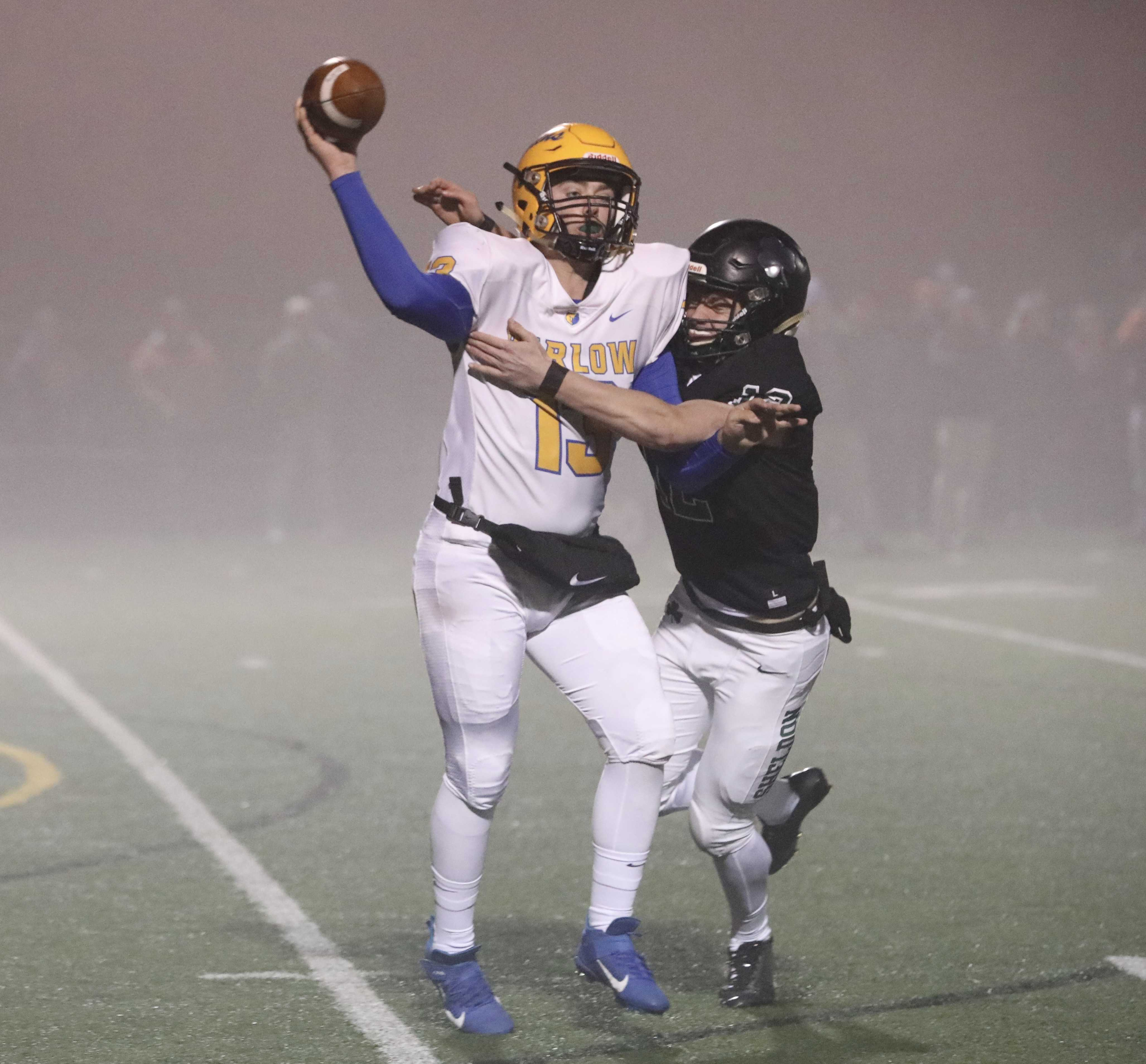 Barlow quarterback Jaren Hunter gets a pass off with Sheldon's Rhys Messner hanging onto him. (Photo by Norm Maves Jr.)