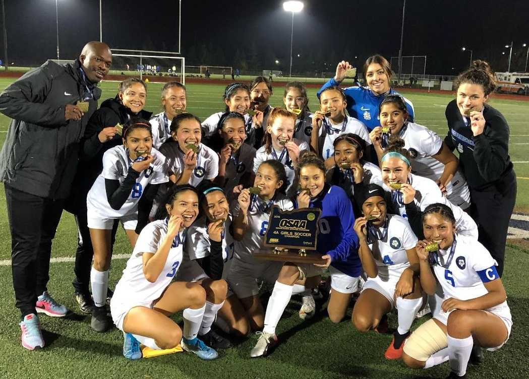 Woodburn's girls pose with their first state championship trophy Saturday. (Photo by Kyle Pinnell)