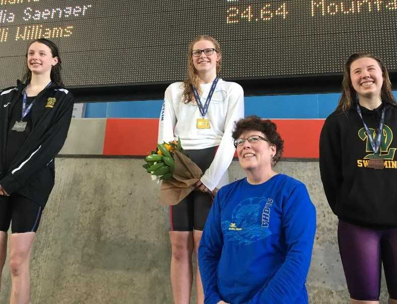 Aloha's Kaitlyn Dobler (center), with coach Lisa Leslie (foreground), reset two of her OSAA meet records Saturday.