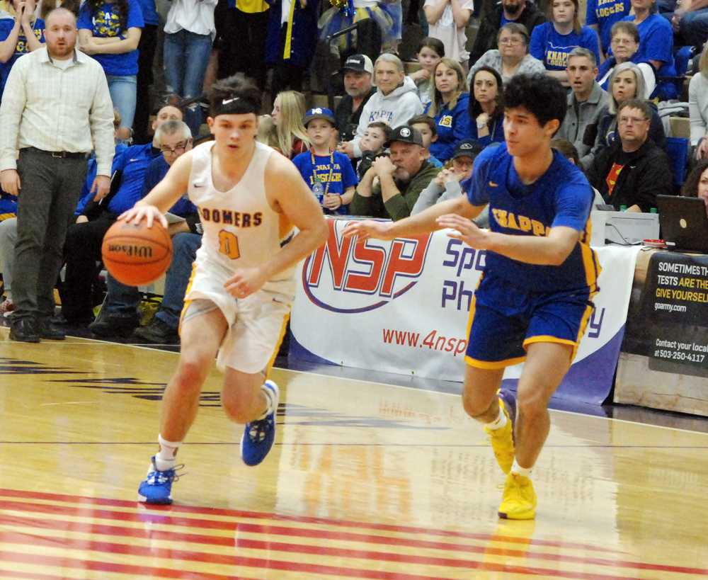 Toledo point guard Conner Marchant (0) dribbles past Knappa guard Kanai Phillip. Marchant scored 28 in the Boomer win