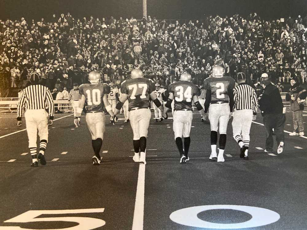 Mike Hass (10) and his fellow Jesuit captains walk to midfield for the coin toss before a packed house