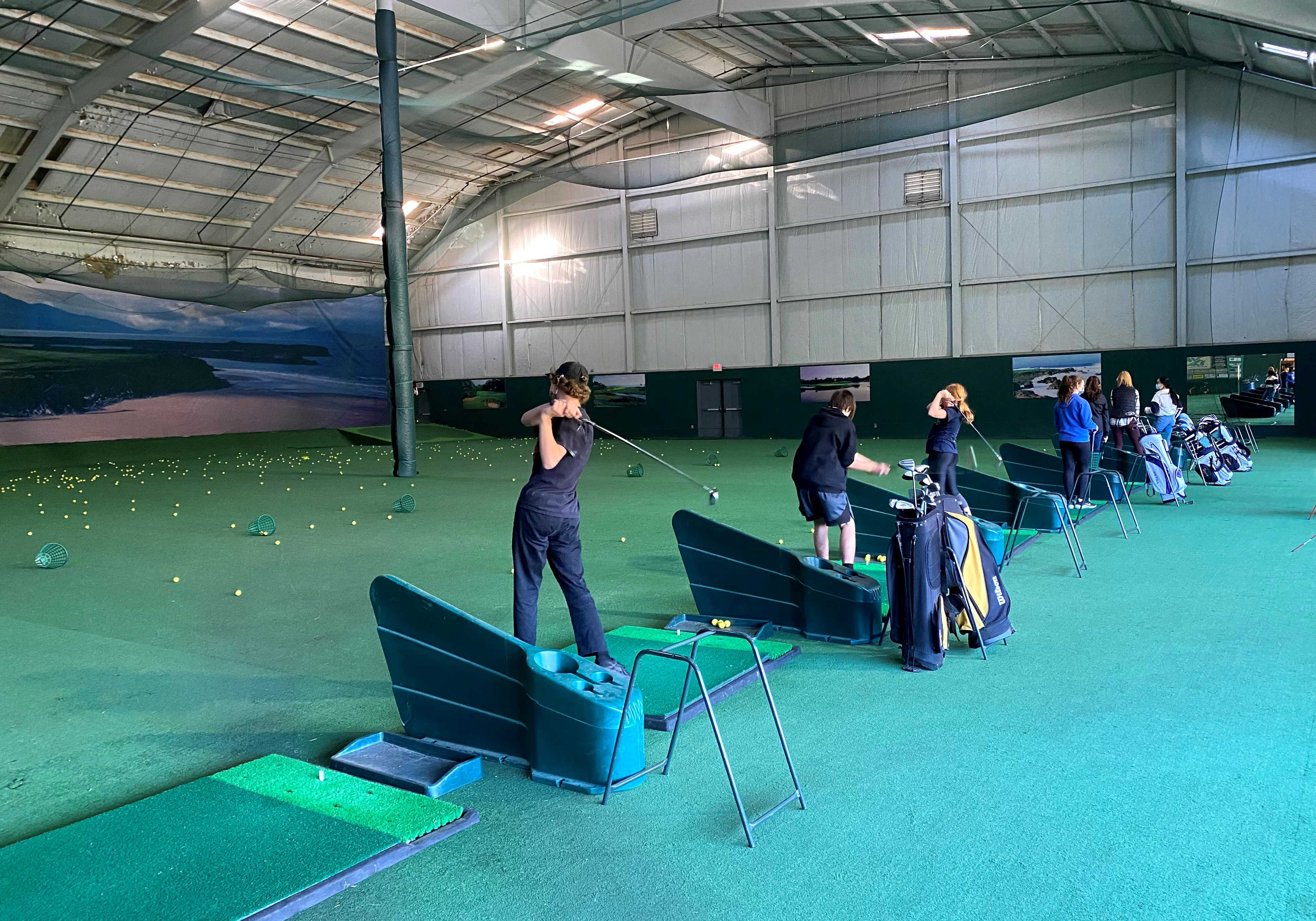 Students practice at the indoor driving range at Chinook Winds Golf Resort on Wednesday in Lincoln City.