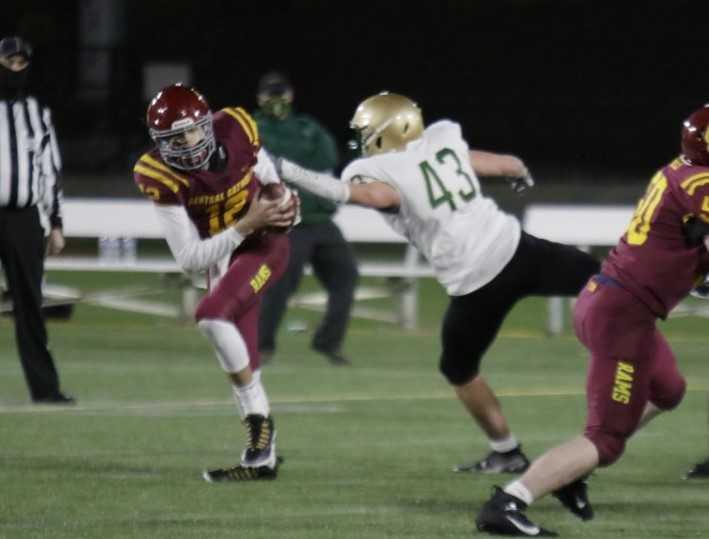 Central Catholic quarterback Luke Johnson avoids the rush of Jesuit's Spencer McKelligon. (Photo by Jim Nagae)
