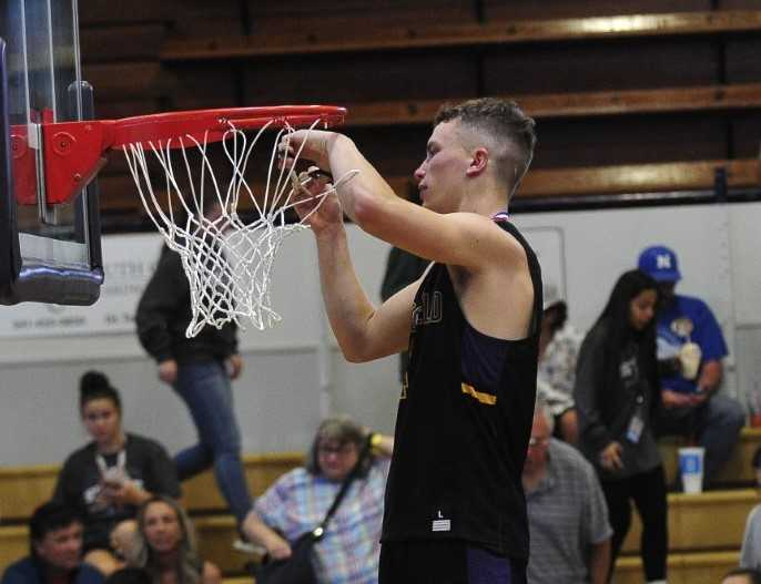 Marshfield's Noah Niblett cuts down the net after his team's win over Cascade on Friday. (Photo courtesy The World)