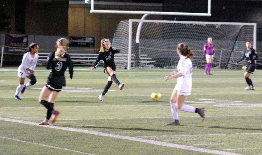 Payton Mongelli (12) moves the ball forward for Clackamas. The Cavaliers won the second-round match, 3-1