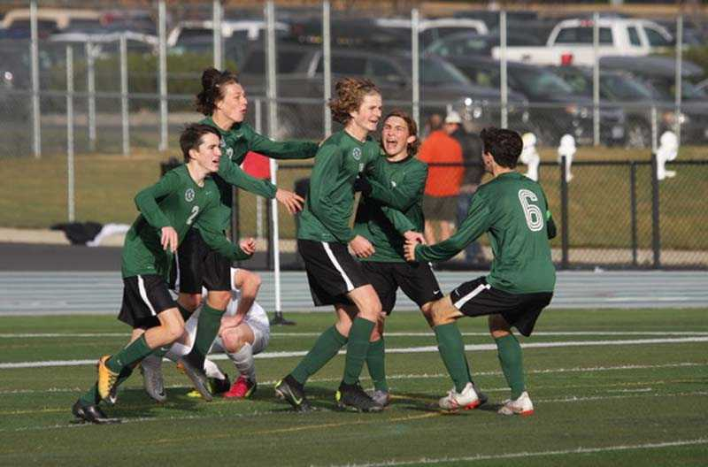Kyle Capdevila celebrates with his Summit teammates after scoring the loan goal in the Storm's 1-0 overtime win