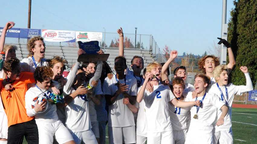 Hansen Lian holds the OSAA championship trophy aloft as his Catlin Gabel teammates celebrate the 3A/2A/1A boys soccer title