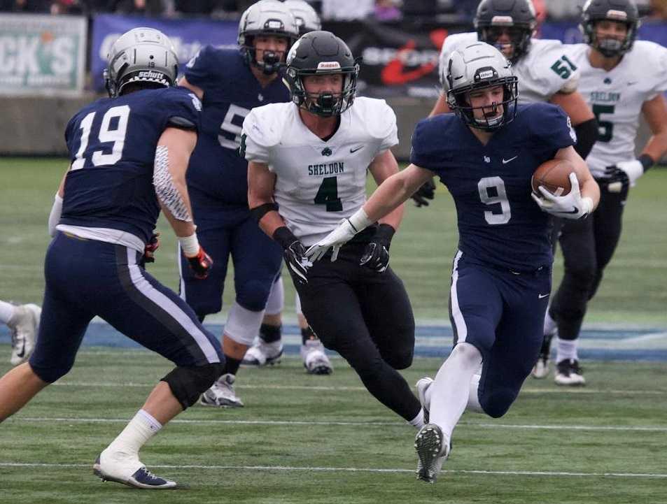 Lake Oswego's Casey Filkins (9) escapes Sheldon's Matthew Burgess (4) on a 40-yard touchdown catch. (Photo by Norm Maves Jr.)