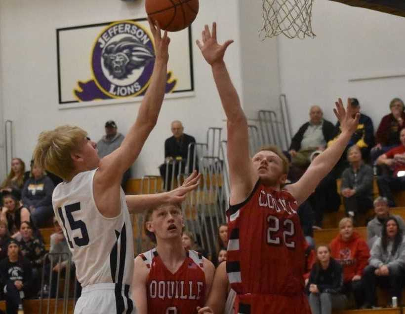 Sheridan's Trevor Lambert (15) drives against Coquille's Ean Smith. (Photo by Jeremy McDonald)
