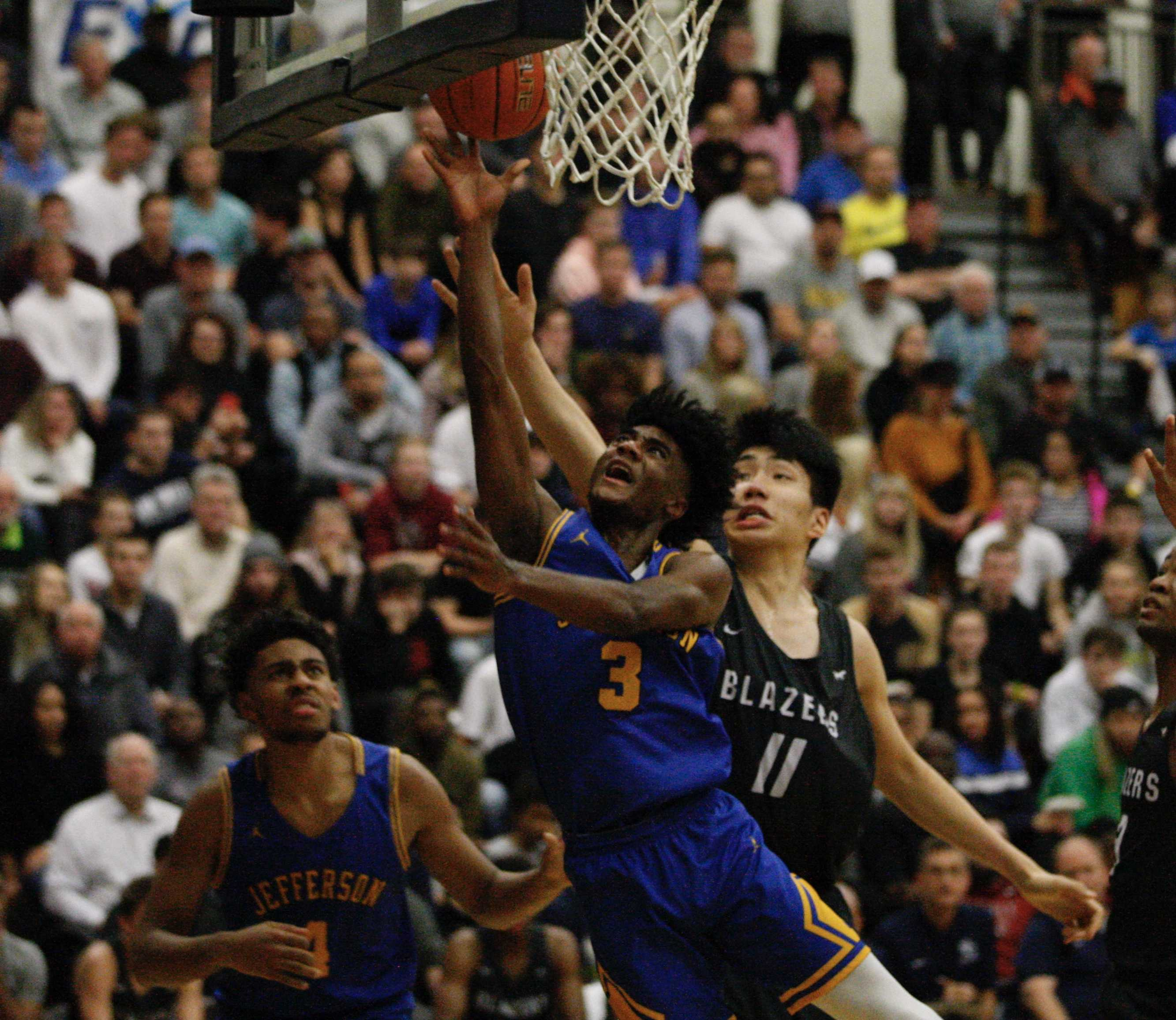 Jefferson's 6-4 Jalen Brown slashes past 7-2 Jia-Hao Yu of Sierra Canyon on his way to a layup. (Photo by Norm Maves Jr.)