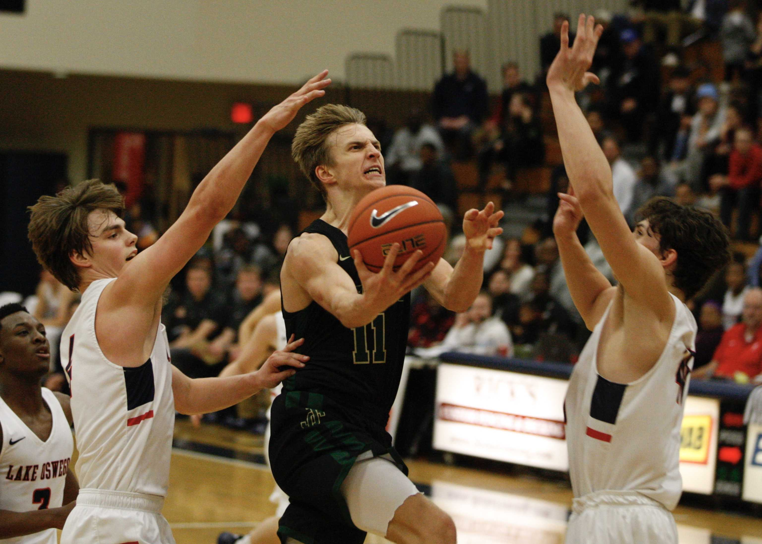 Jesuit's Will Sheaffer gets between Brandon Roberts (left) and Fred Harding IV of Lake Oswego for a crucial second-half layup.