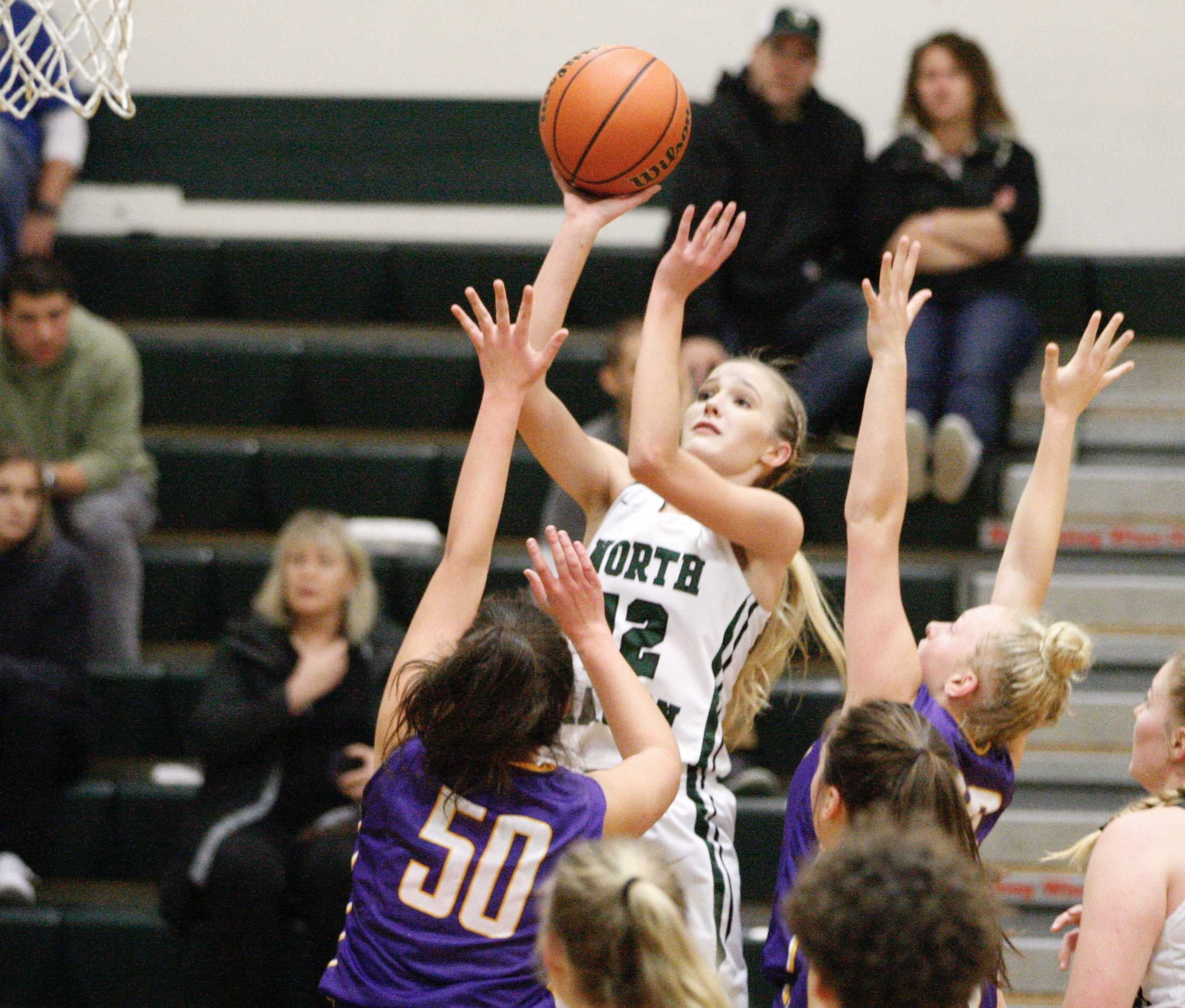 North Marion junior Katie Ensign goes over Gracie Brugnoli (50) and McKayla Myrand of Marshfield for two of her 18 points.
