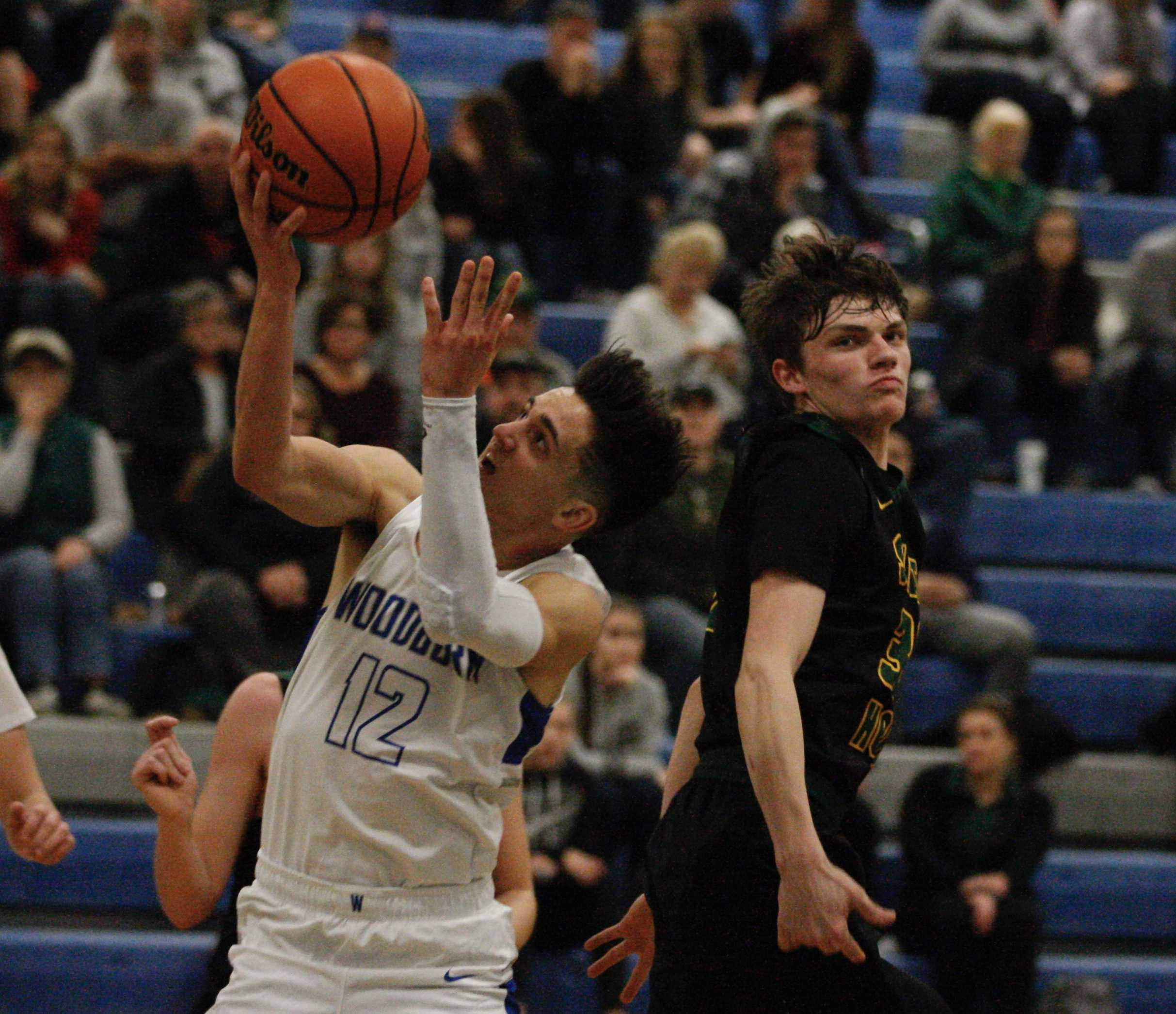 Woodburn's R.J. Veliz corkscrews past Sweet Home's Jake Swanson for two of his game high 23 points. (Photo by Norm Maves Jr.)