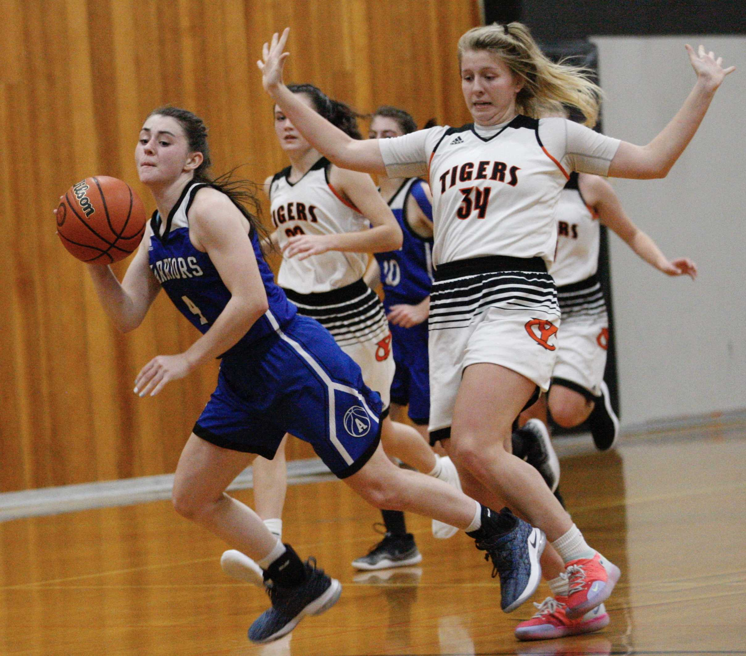 Amity's Keeley Graham (left) goes flying after getting tripped up by Yamhill-Carlton's Sadie Horne on Tuesday night.