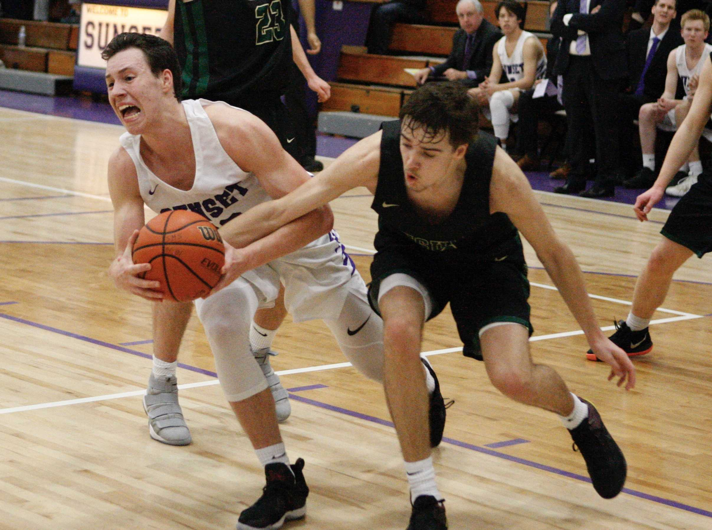 Sunset's Colby King wrestles the ball away from Jesuit's Justin Bieker in the third quarter of Apollos' 89-84 victory.