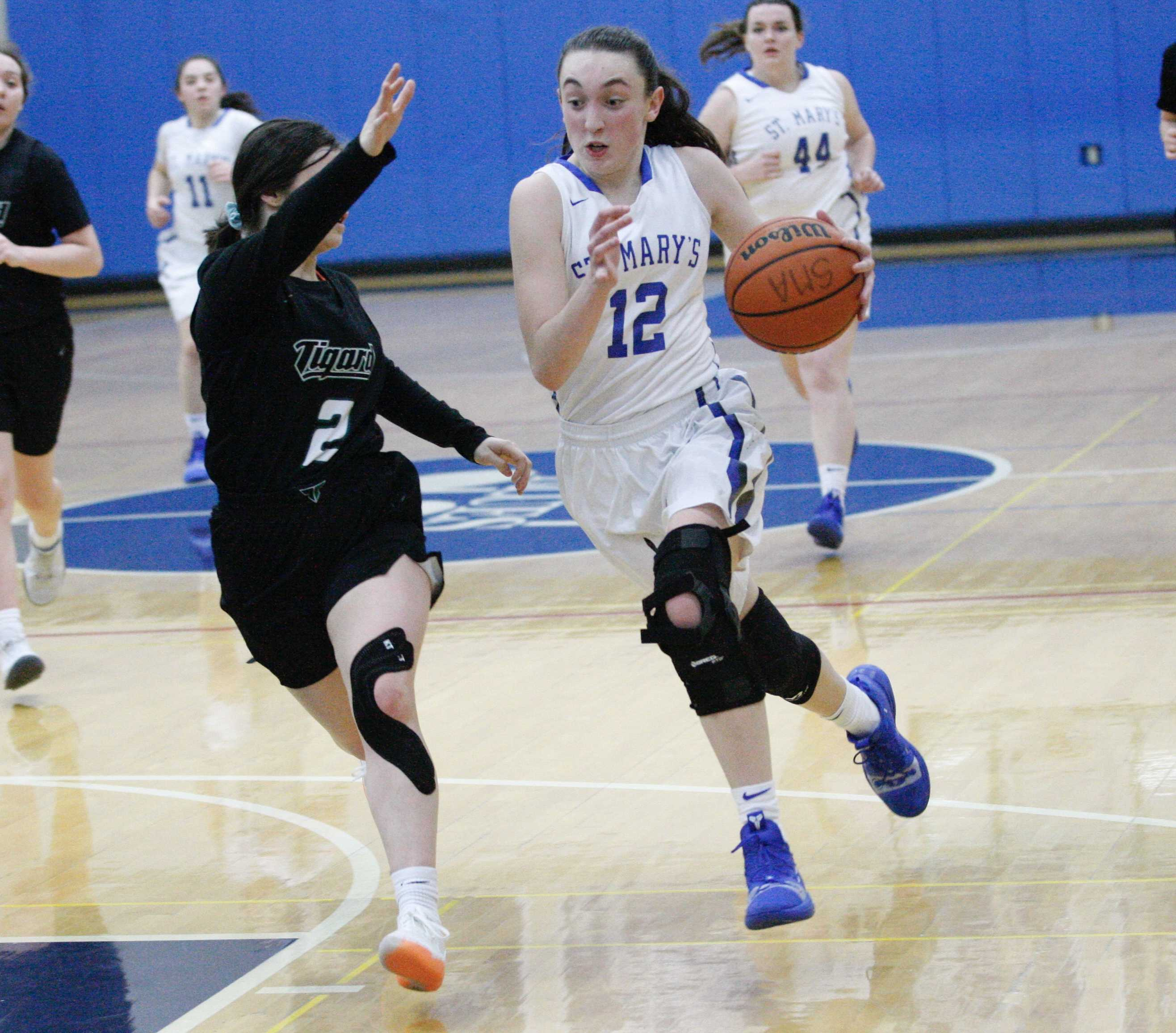 St. Mary's Academy's Anna Eddy drives into Tigard's Kennedy Brown on her way to a 14-point night. (Photo by Norm Maves Jr.)