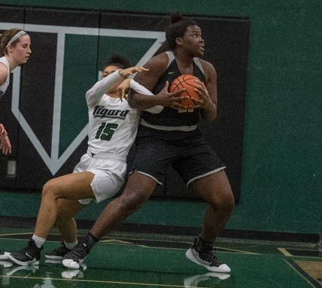 West Linn's Aaronette Vonleh fights through Tigard's Ajae Holdman on her way to the basket. (Photo by Ralph Greene)