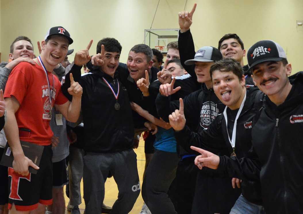 Tillamook coach Lonnie Eggert (center) and his team celebrate the Special District 1 title. (Photo by Matt Dickson)
