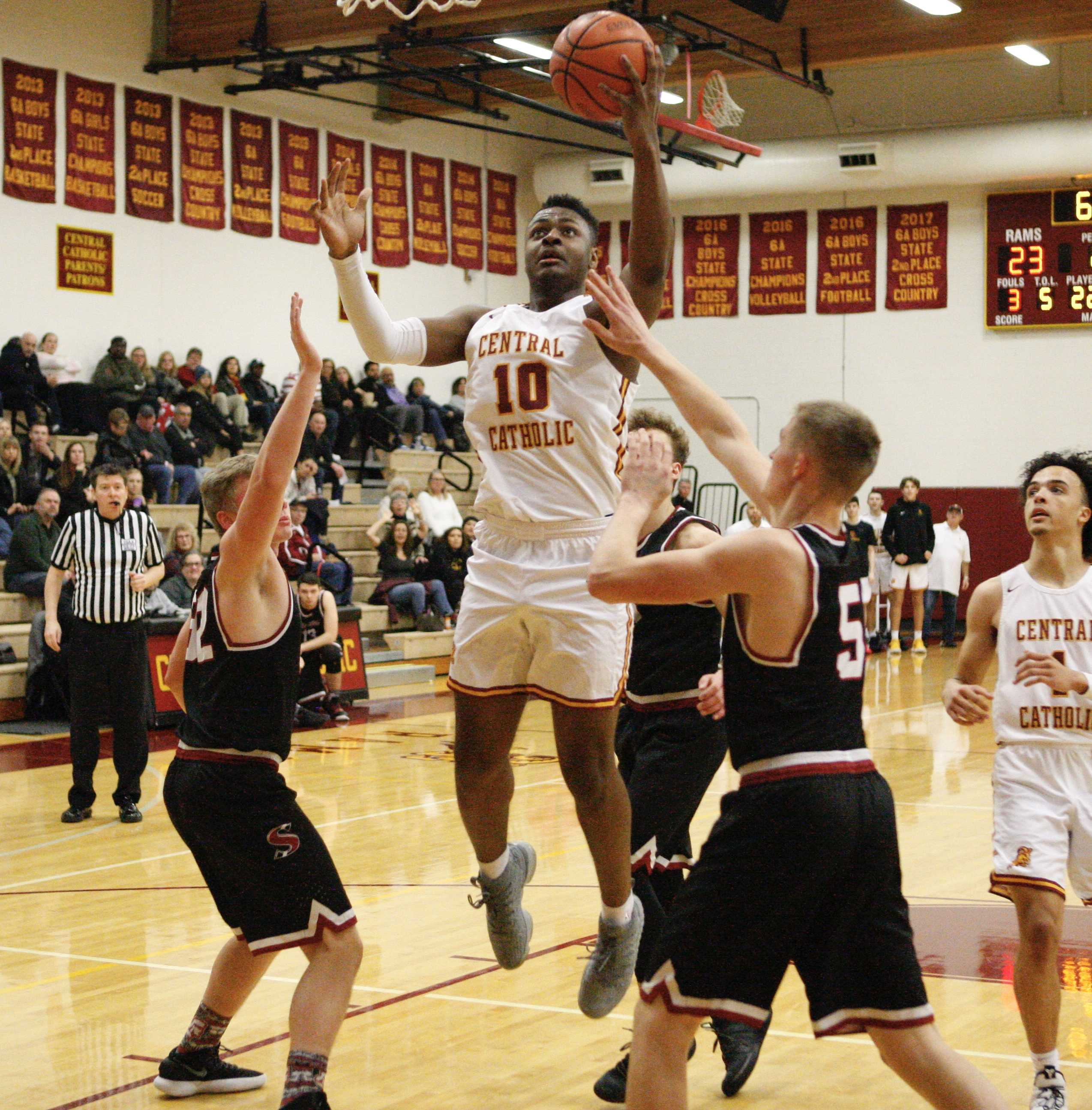 Central Catholic junior SataieVior Ayilola skies over three Sandy defenders for two of his 17 points.