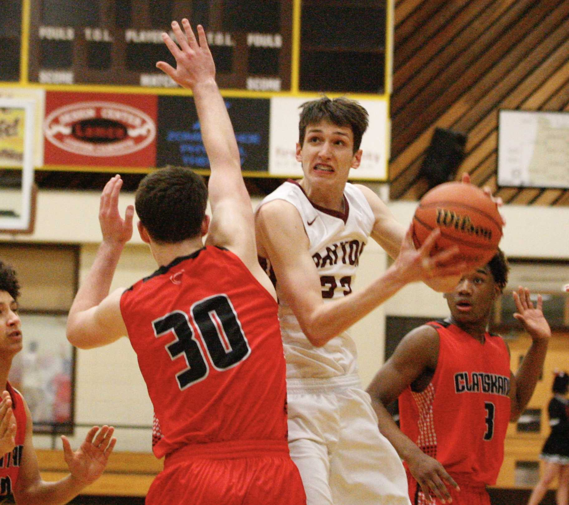 Dayton's Jaysen Howard gets between two Clatskanie defenders for a scoop shot Thursday. (Photo by Norm Maves Jr.)