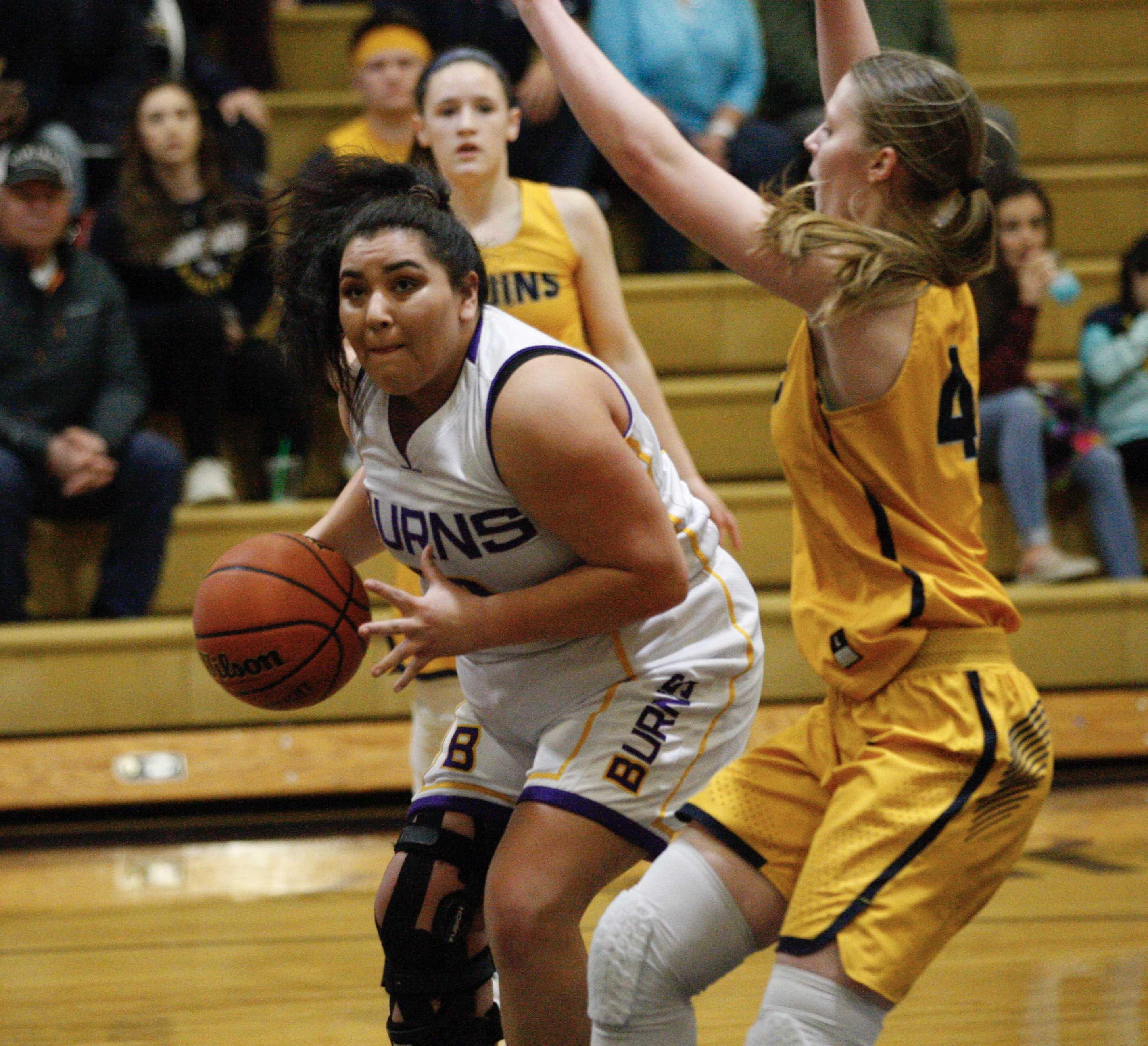 Burns forward Maliah Skunkcap muscles past the defense of Brookings-Harbor's Chloe McCrae. (Photo by Norm Maves. Jr.)