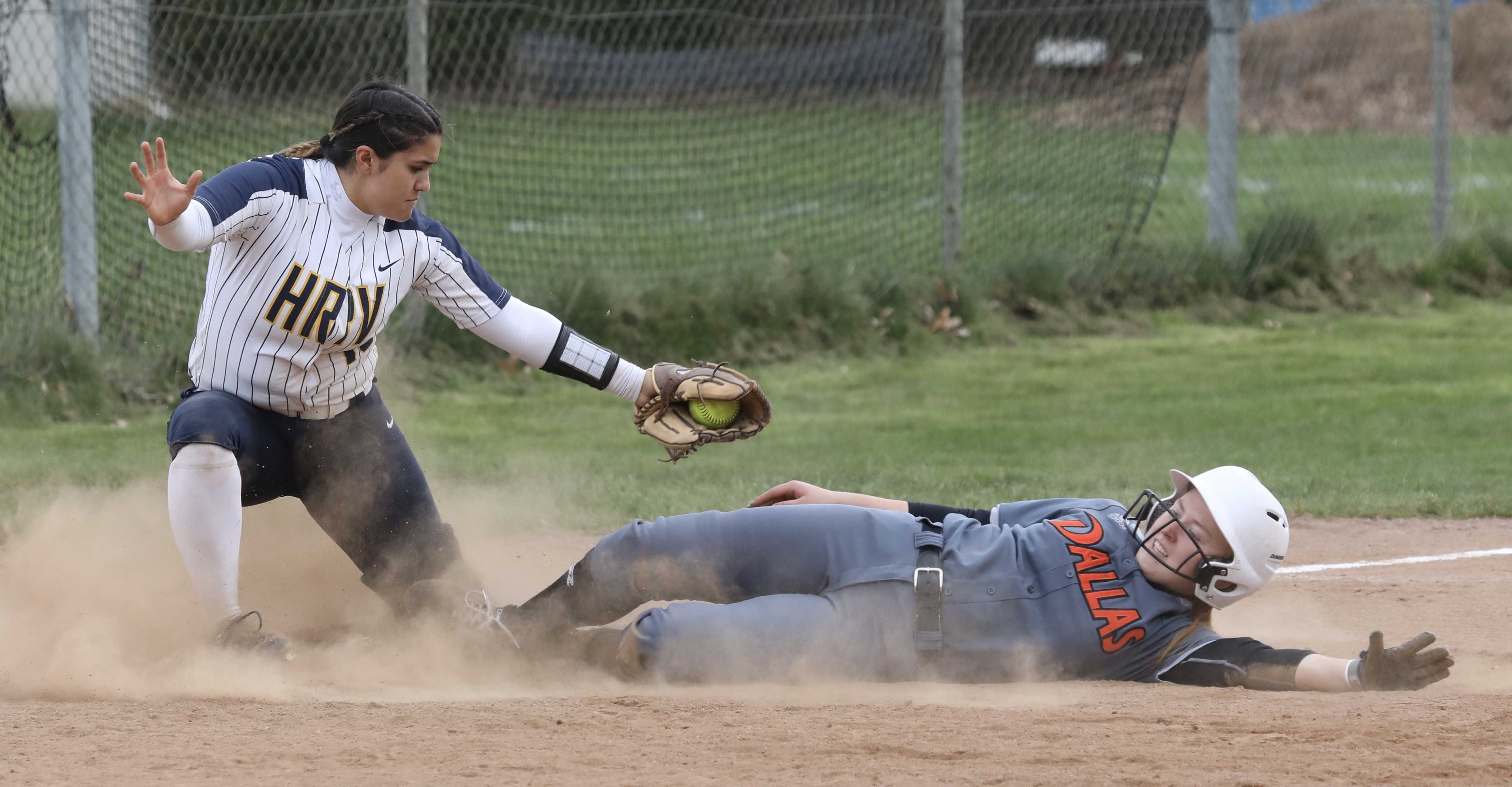 Dallas sophomore Morgan Dippel slides safely under the tag of Hood River Valley third baseman Aunika Yasui during Dragon rally.