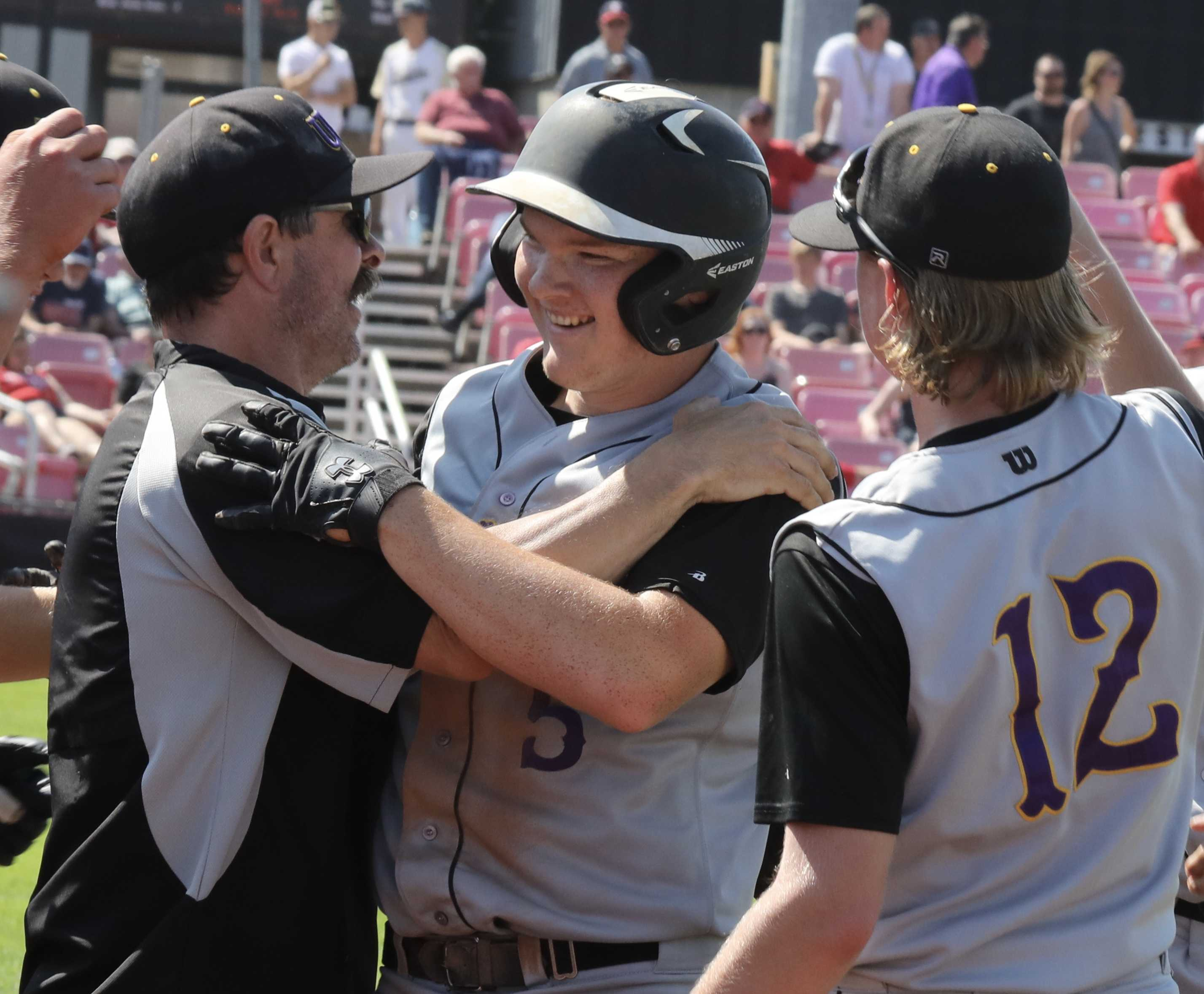 Umpqua Valley Christian's Isaiah Heard gets the cheers of a Monarch coach and teammate Jacob Luther after key two-run double