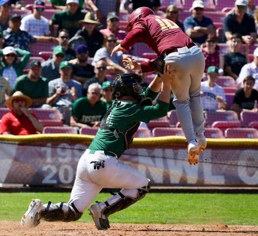 Central's Mason Smith attempts to score by jumping over Jesuit catcher Joe Angeli
